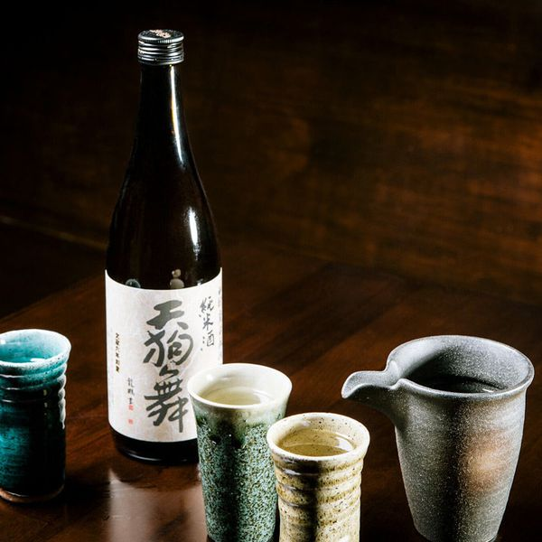A sake bottle on a dark brown surface surrounded by traditional Japanese ceramic vessels