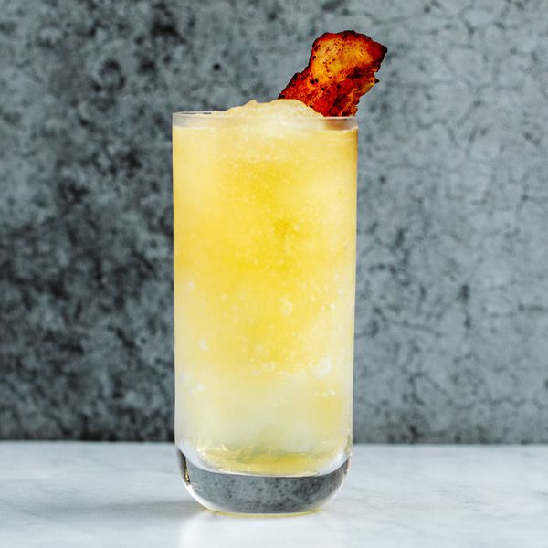 A clear Collins glass filled with a bright yellow slushie and garnished with crisp bacon