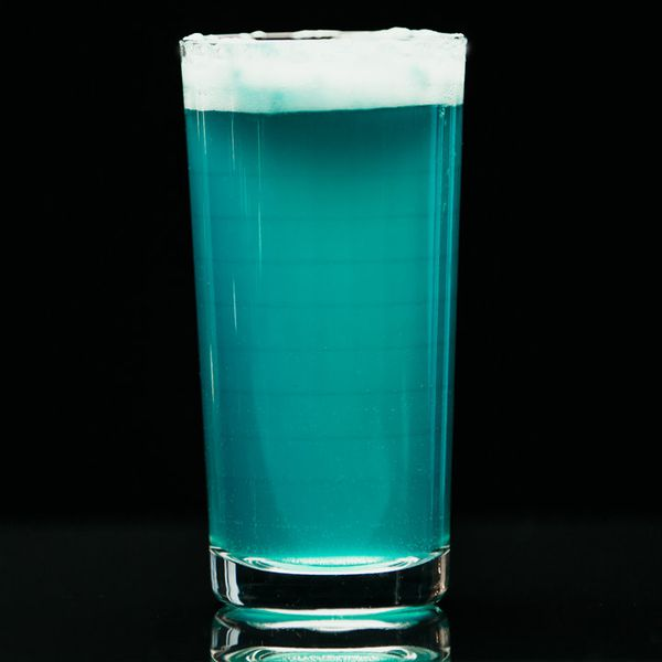 blue-colored Romulan Ale Fizz cocktail with a frothy white head, served in a Collins glass on a black background