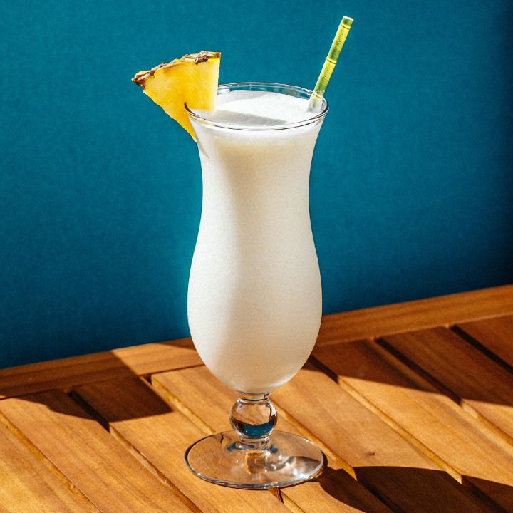 A curvy Hurricane glass rests on a slatted wooden surface against a sea blue wall. The glass holds a pale white blended coconut cocktail and is garnished with a pineapple wedge and a yellow and green straw.