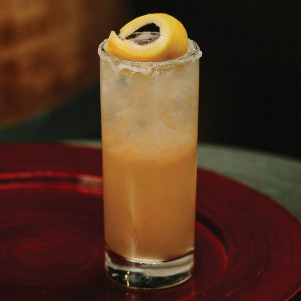 salty dog cocktail served on a red circular tray