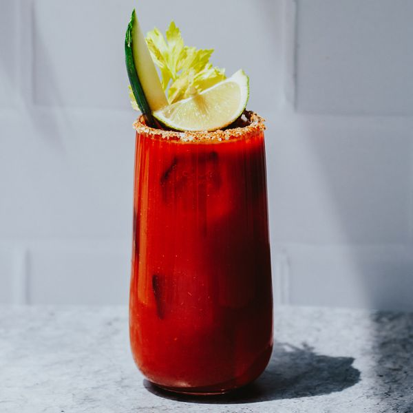 Deep red Bloody Caesar cocktail with lime and celery garnishes