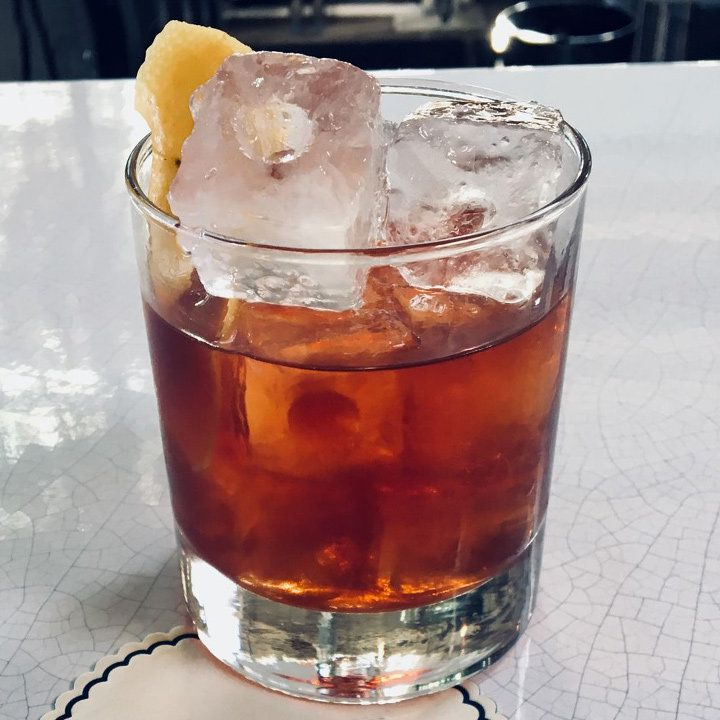 A rocks glass sits on a white bar top. It's filled with ice cubes with holes in the middle of them, as well as a ruddy drink and a lemon peel.