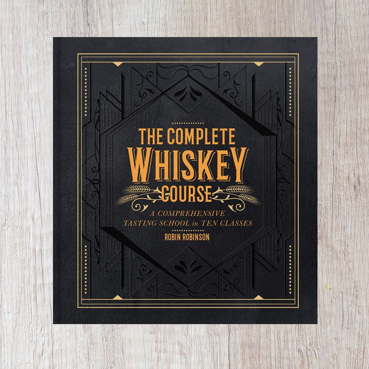 The Complete Whiskey Course cover with black filigree and orange text and accents. The cover is framed by a light wood graphic pattern