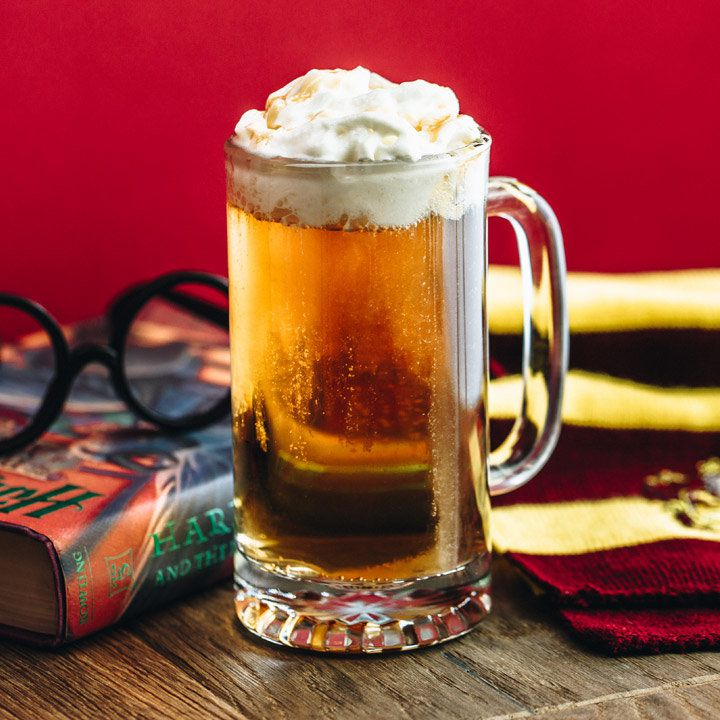 butterbeer cocktail in a mug next to harry potter book and glasses