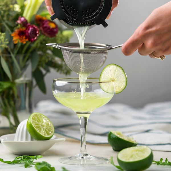 Cocktail pour into coupe glass with limes