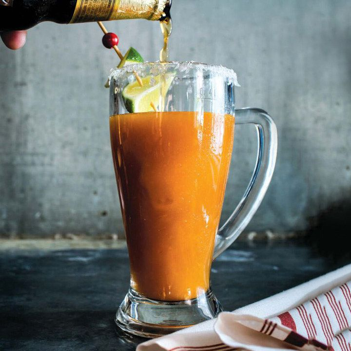 hand pours a dark beer into the orange-colored Shannon's Sangrita/Michelada, served in a beer mug with skewered lime garnish beside a cloth napkin