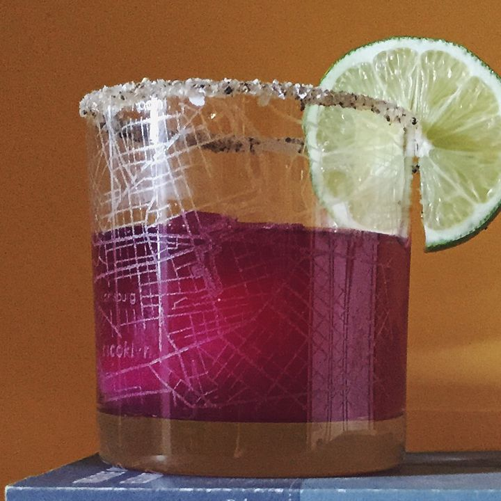 purple colored Shrubarita cocktail in a salt-and-pepper-rimmed rocks glass with a lime wheel garnish