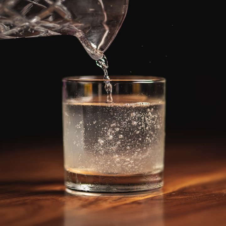 A viscous, silky cocktail bubbles slightly as it is poured over a crystal-clear ice cube in an unadorned rocks glass. The drink sits on hard wood which fades into a pitch black background.