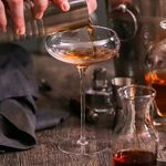 A hand pouring a Manhattan into a long-stemmed coupe glass from a mixing tin.