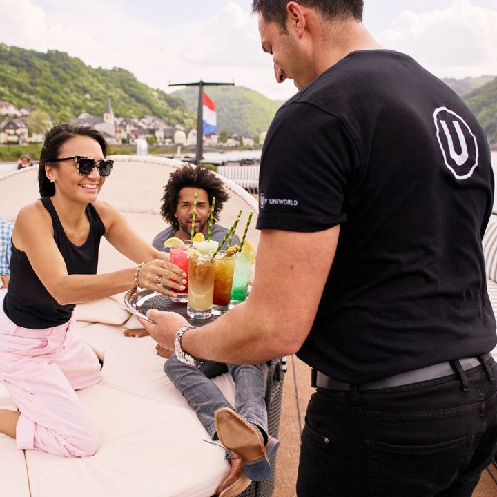 U by Uniworld daybeds with a pair of guests being handed some tropical long drinks