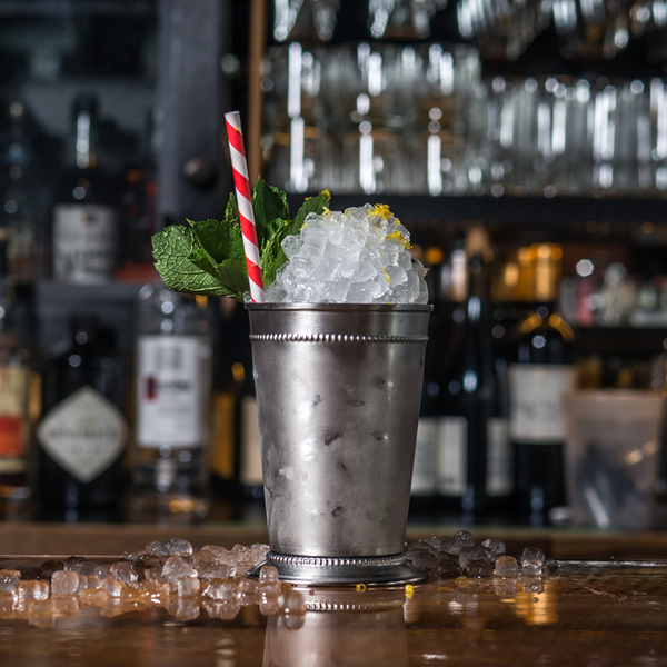 Napoleon Julep cocktail in a silver julep cup, with crushed ice, mint and a red-and-white straw