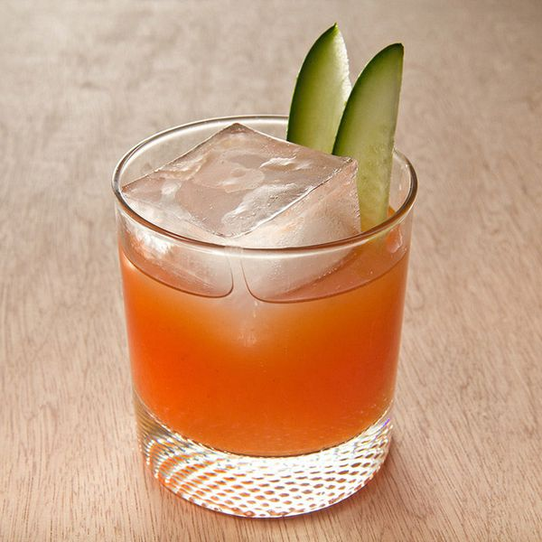 A rocks glass sits on a light colored wooden surface. In it is a bright orange tomato drink, a single large ice cube, and to slivers of cucumber.