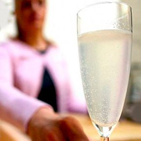 A woman wearing a pink sweater is out of focus in the background. She extends a champagne flute full of a slightly opaque bubbling drink towards the camera.