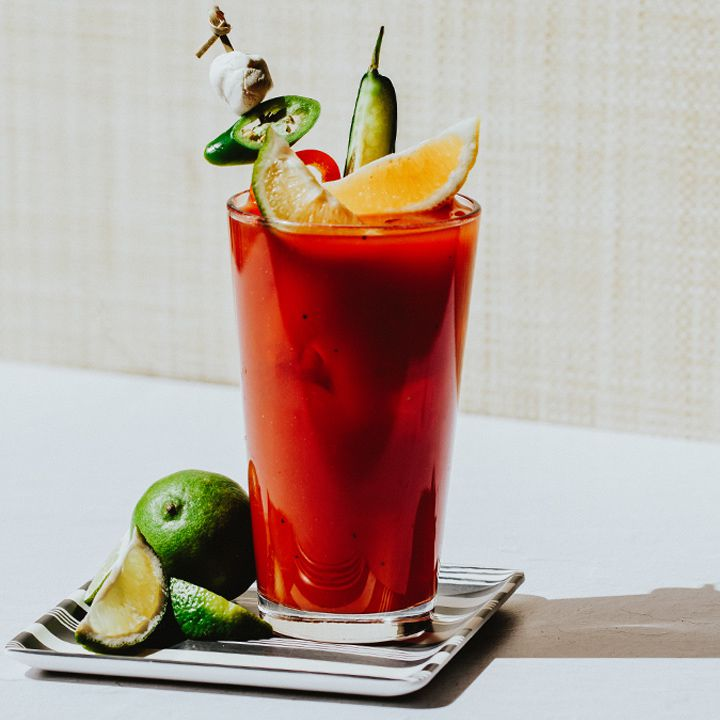 Bloody Maria on a striped coaster, garnished with citrus and peppers
