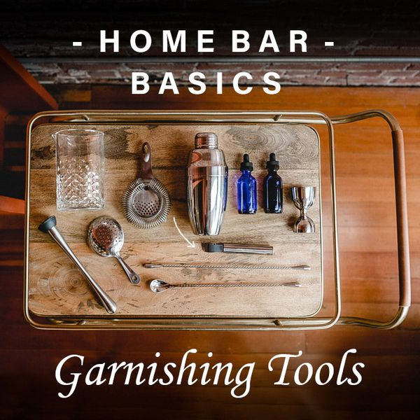A cocktail mixing glass, two strainers, a shaker, peeler, two stoppered glass bottles, a metal jigger, two long-handled bar spoons, and a muddle rest on an elegant wooden bar tray with brass handles. A text overlay reads Home Bar Basics, Garnishing Tools.