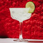 Hemingway Daiquiri with lime wheel set against red background