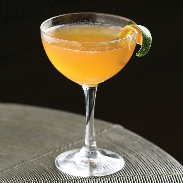 A coupe glass containing a shaken orange Tiki drink, garnished with two citrus twists