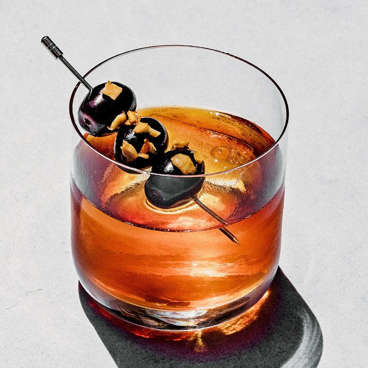 A thin-walled rocks glass rests on a gray surface. It's filled with a dark red drink over a single large ice cube, and garnished with three Concord grapes on a pick, sprinkled with almond..