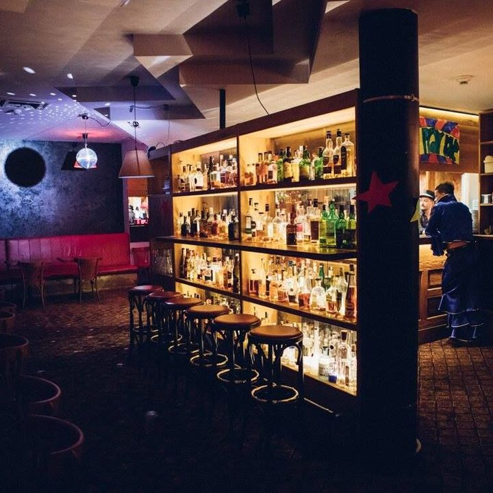 The Bar Which Doesnt Exist, looking onto a beautifully backlit collection of booze bottles with stools in front of it