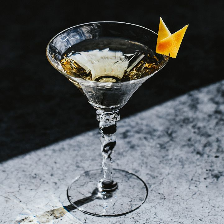 50/50 martini with a lemon twist, served in a cocktail glass on a stone bar top