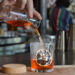 A bartender pouring a ruby-red cocktail into a rocks glass containing a dehydrated citrus wheel