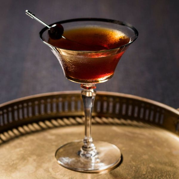 reverse manhattan cocktail in a cocktail glass with skewered cherry garnish, served on a round metal tray