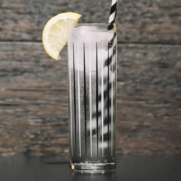 vodka soda cocktail with lemon wedge and black-and-white-striped straw