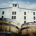 A view of the Jack Daniel's barrelhouse's white façade with whiskey barrels in the foreground.