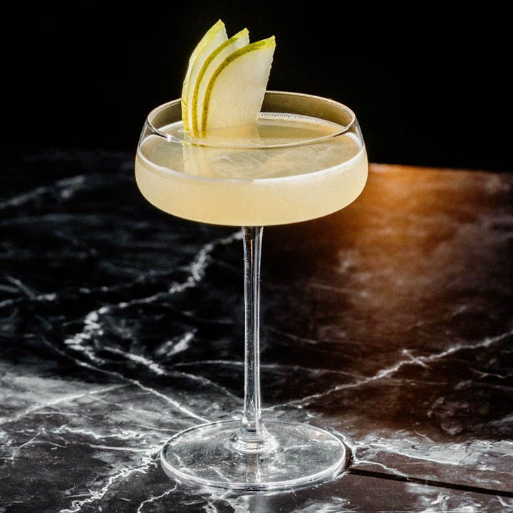 A wide and shallow coupe with a long, thin stem rests on a black marble surface. The glass holds a pale yellow cocktail and three slices of pear. The background is solid black.
