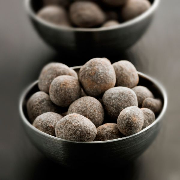 two gray bowls filled with Bourbon Balls served on a gray surface