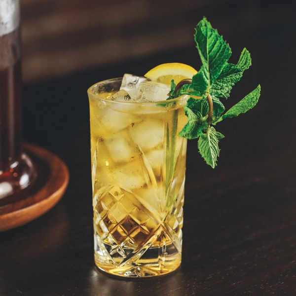 A detailed highball glass holds a bourbon-spiked sweet tea, a number of medium-sized ice cubes, a lemon wheel, and a sprig of mint, which drapes over the glass. The background is dark hard wood.