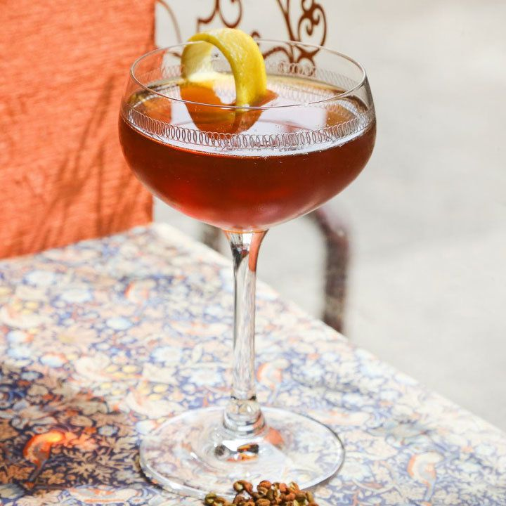 A stylish cocktail coupe rests on a colorfully patterned table cloth. The etched glass holds a reddish brown drink and is garnished with a lemon peel.