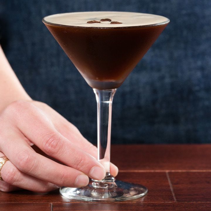 hand holding the stem of an espresso martini cocktail