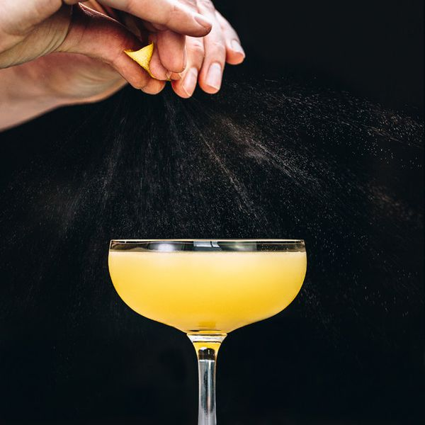 hands express lemon peel oils over the Applejack Rabbit cocktail, served in a coupe glass