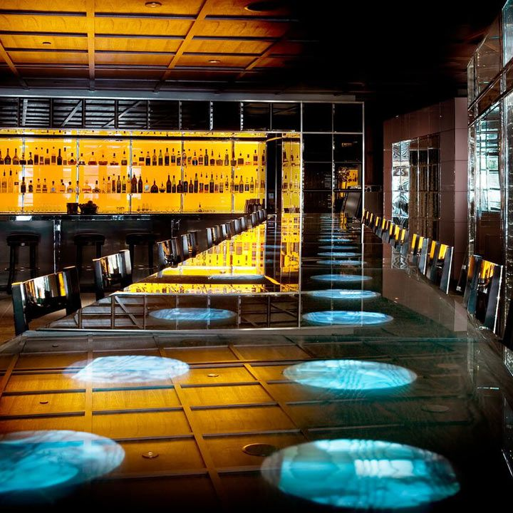 Bar Centro interior, with yellow backlit bottle collection and a long communal table