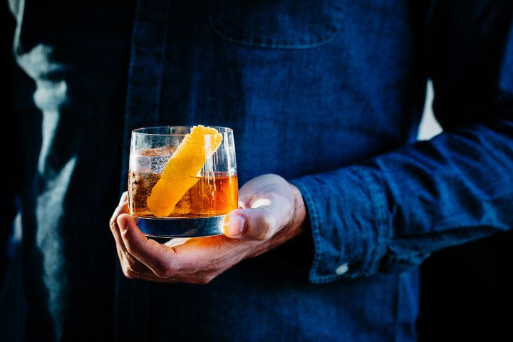 A denim shirt-clad person holding a drink in a rocks glass garnished with an orange twist