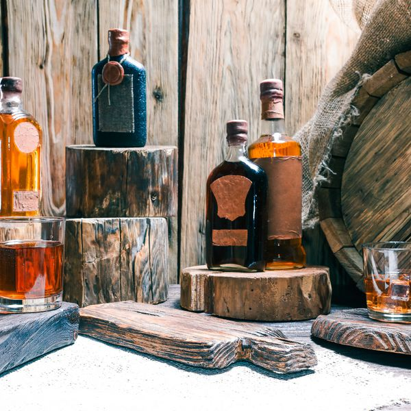 Rum and brandy bottles and whiskey glasses on raw wood bar counter.