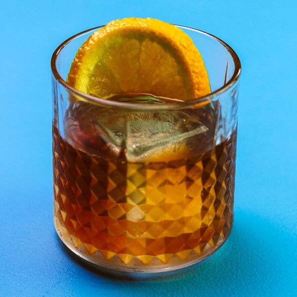 On a sold blue backdrop, a multi-faceted rocks glass holds a single large ice cube, a full orange wheel, and an amber-colored bourbon drink.