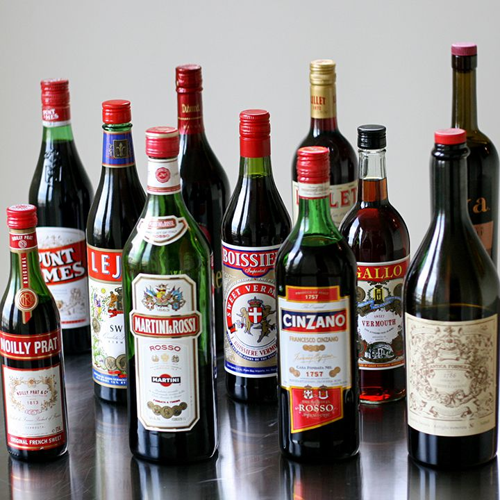 A group of 11 sweet vermouth bottles on a steel surface