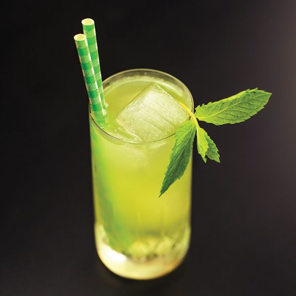 A lime green-hued gin cocktail in a Collins glass with an ice spear, a sprig of mint and two green paper straws