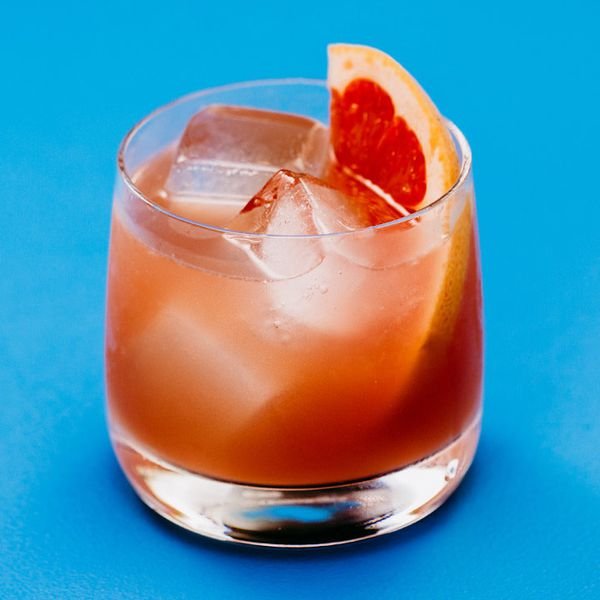 A double Old Fashioned glass is against a solid sky-blue backdrop. The glass is filled with a few large ice cubes, a juicy orange drink and a thin slice of grapefruit.