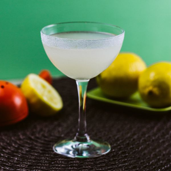 An elegantly curved coupe with a sugared rim is filled with a lightly a bright Lemon Drop. Surrounding it are a variety of lemons, as well as a red lemon squeezer
