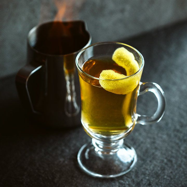 A clear glass cocktail mug filled with light brown liquid and garnished with a lemon twist; a metal pitcher with flames coming from within it sits to the left of the mug.