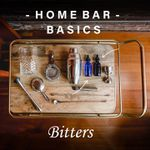 """A collection of bar equipment rests on an elegant wooden bar tray with brass handles. The tray holds a shaker, mixing glass, two strainers, two stoppered blue bottles, a jigger, peeler, two bar spooners, and a muddler. The words """"Home Bar Basics"""" and """"Bitters"""" are printed above and below the tray."""