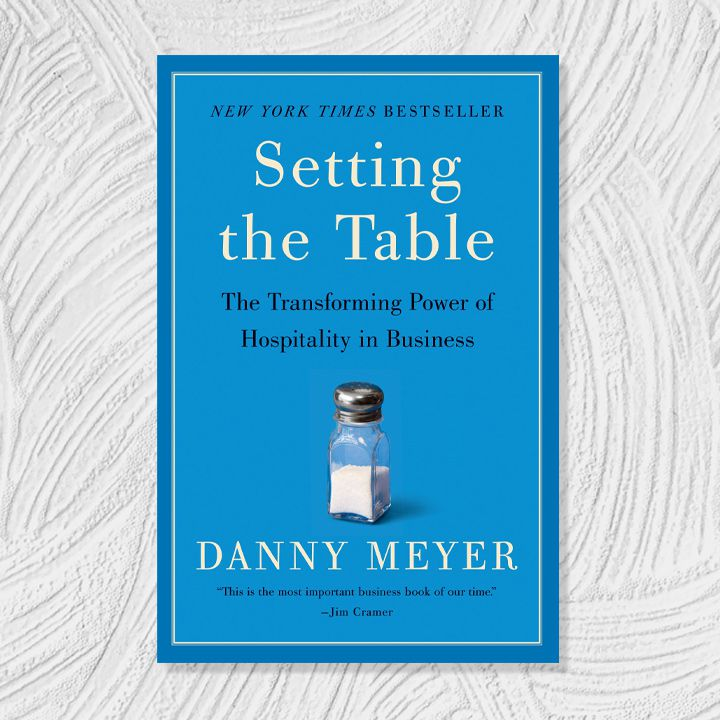 Setting the Table cover, light and dark blue background with black and white serif text around a small image of a salt shaker