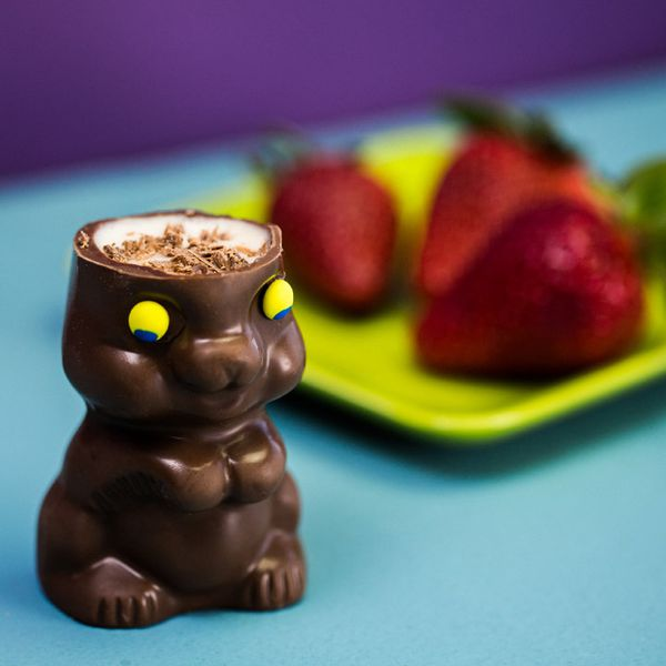 In the foreground, a chocolate Easter bunny with yellow eyes and no top of its head is filled with white liquid and dusted with chocolate. In the background, out of focus, is a yellow plate with three fresh strawberries on top.