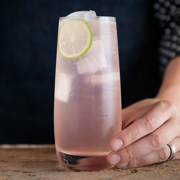 Hand with silver ring places paloma cocktail on a wooden surface