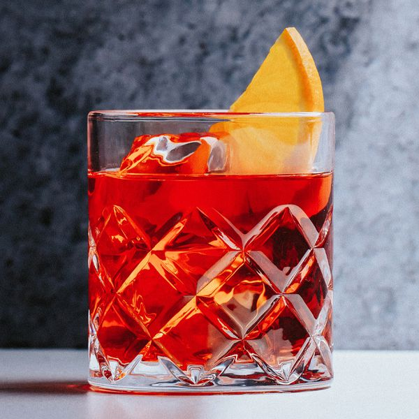 A sturdy looking rocks glass is filled with clear ice and the iconic crimson-hued Negroni, and is garnished with a slice of orange. The background is gray.