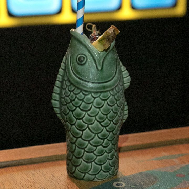 A Tiki mug in the shape of a green fish, its mouth the mouth of the cup. A pineapple and cherry garnish, as well as a blue and white-striped straw, extend upwards from its mouth.